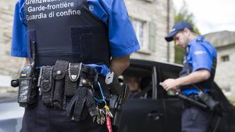Grenzwächter kontrollieren die Papiere eines Fahrers.
