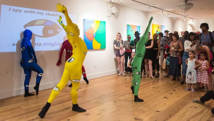 Rote, gelbe, grüne und blaue Gestalten in Morph Suits mischen sich unter die Menschen.