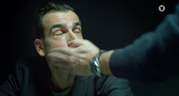 Eine verhörte Person erhält eine Ohrfeige von Reto Flückiger. (Screenshot ARD)