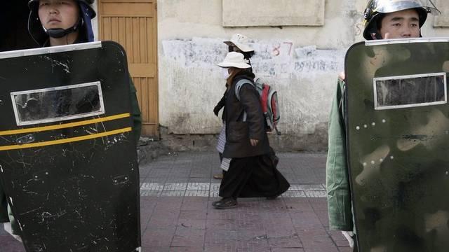 Tibetische Frauen gehen in Lhasa an chinesischen Paramilitärs vorbei