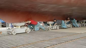 340 Tonnen Stahl werden mit Muskelkraft aus der Werfthalle gerollt, damit der Kran Zugang zu den Aufbauten hat.