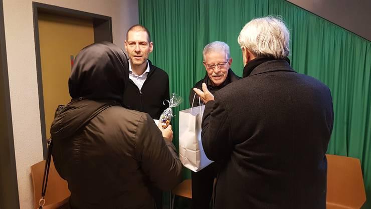 Die Rotarier Daniel Arber und Franz Hunkeler übergeben armutsbetroffenen Menschen ihre guten Wünsche sowie ein Weihnachtspaket mit Lebensmitteln und etwas Bargeld.