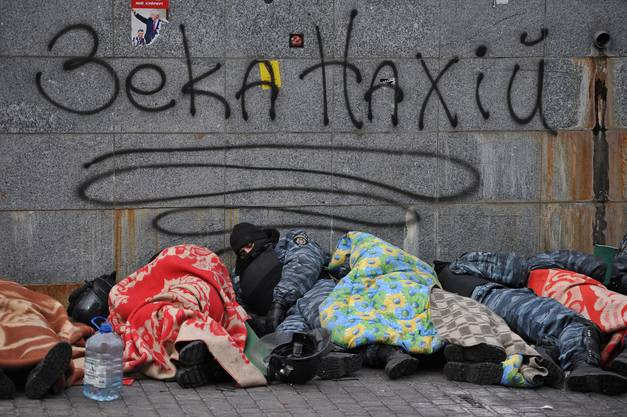 Polizisten schlafen unter einem Graffiti auf dem Unabhängigkeitsplatz.