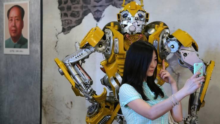 Eine chinesische Frau posiert für ein Selfie mit einem Transformer. Im Hintergrund das Porträt von Mao Zedong.