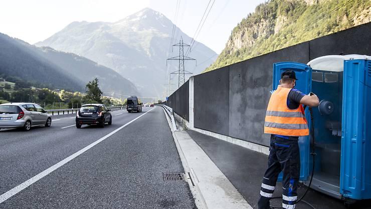 Alexandar Djordjevic reinigt mobile Toilettenkabinen direkt an der Autobahn A2 vor dem Gotthard-Nordportal bei Wassen.