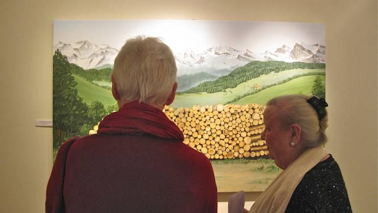 """Magdolna Keel zeig ihre Gemälde:""""Holzscheite vor Bergpanorama"""" einer Besucherin der Ausstellung"""