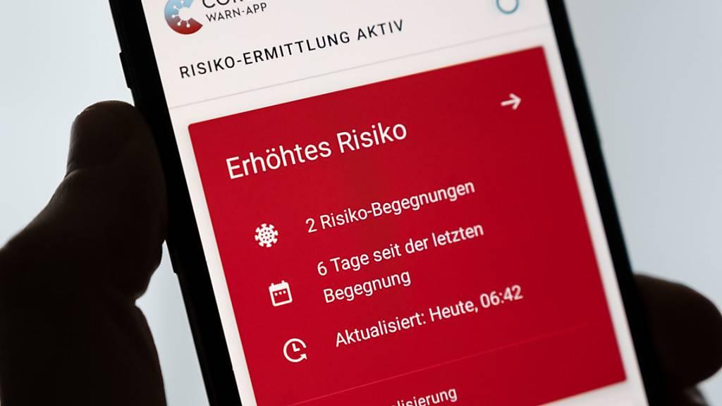 Ein Mann hält ein Smartphone in der Hand, auf dem die Corona-Warn-App der Bundesregierung ein erhöhtes Risiko anzeigt. Foto: Marius Becker/dpa