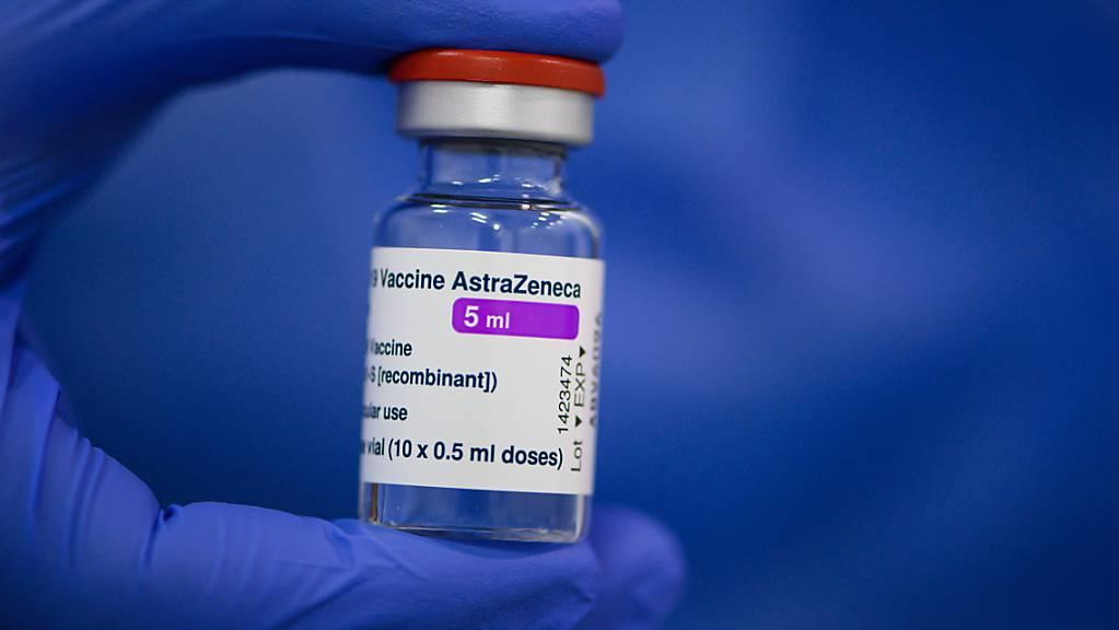 ARCHIV - Ein Mitarbeiter in einem Impfzentrum hält ein Fläschchen mit dem Astrazeneca-Wirkstoff gegen Corona in seiner Hand. Foto: Robert Michael/dpa-Zentralbild/dpa