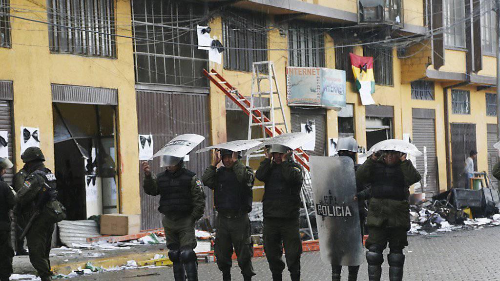 Polizisten sichern das Gebäude der Stadtverwaltung, in dem bei einer Demonstration ein Feuer ausbrach. Sechs Personen starben.