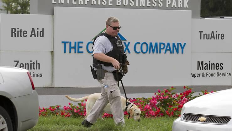 Ein Polizist sucht mit seinem Hund am Tatort nach Spuren.