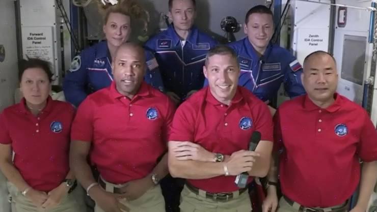 HANDOUT - Der Bildausschnitt von NASA-TV zeigt die Crew von SpaceX Dragon (vorne,l-r), Shannon Walker, Victor Glover, Mike Hopkins und Soichi Noguchi sowie die Crew der Internationalen Raumstation (hinten,l-r) Kate Rubins, Expedition 64-Kommandeur Sergey Ryzhikov und Sergey Kud-Sverchkov. Foto: -/NASA-TV/AP/dpa