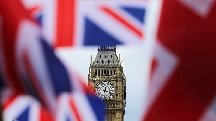 Britische Fahnen wehen vor dem berühmten Uhrturm Big Ben.