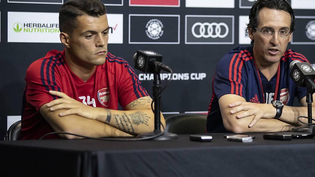 Arsenals Granit Xhaka sitzt an einer Pressekonferenz neben Trainer Unai Emery