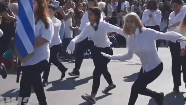 Videos zeigen, wie die zehn Mädchen aus Athen bei der Schüler- und Militärparade an verdutzten offiziellen und kirchlichen Würdenträgern vorbeiwackeln, -hüpfen, -hinken und -schweben. (Screenshot)
