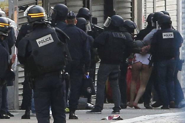 Die Polizei führt einen offensichtlich verletzten, leicht bekleideten Mann aus der besetzten Wohnung ab.