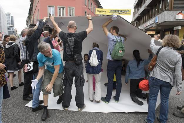 Der Künstler faltet zusammen mit Passanten aus Milchkarton ein Schiff.