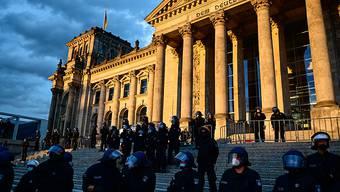 Polizisten stehen bei einem Protest gegen die Corona-Maßnahmen vor dem Reichstagsgebäude. Foto: Fabian Sommer/dpa