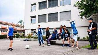 Auf dem Pausenplatz der Bezirksschule Reinach vergnügen sich die Schüler.
