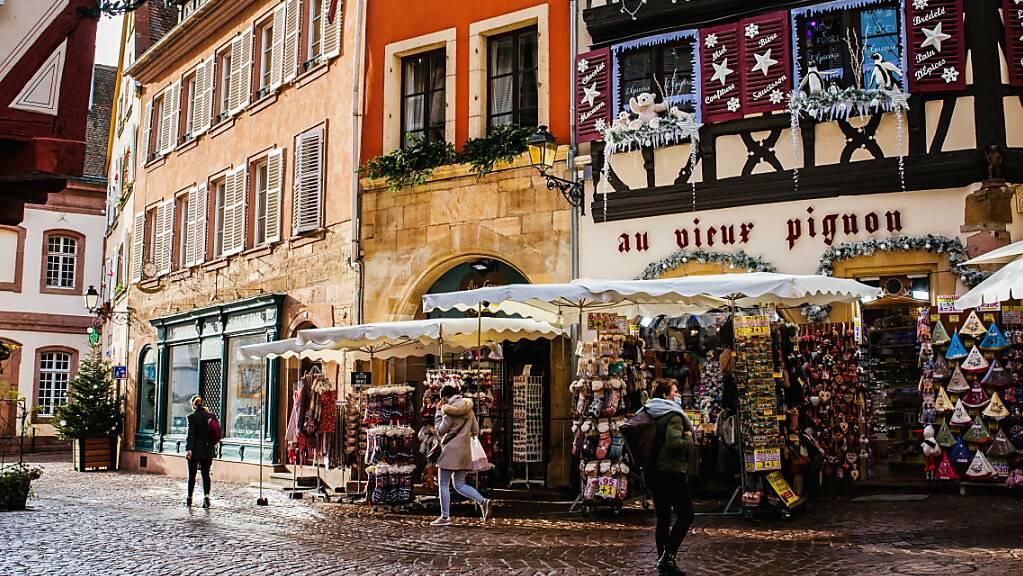 Menschen gehen in der Altstadt von Colmar an Geschäften vorbei. Im Elsass gilt ab Sonntag wegen des Coronavirus eine verschärfte abendliche Ausgangssperre. Foto: Philipp von Ditfurth/dpa