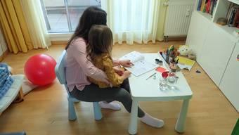 Katharina Huber (Name geändert) mit ihrer Tochter beim Unterricht im Wohnzimmer.
