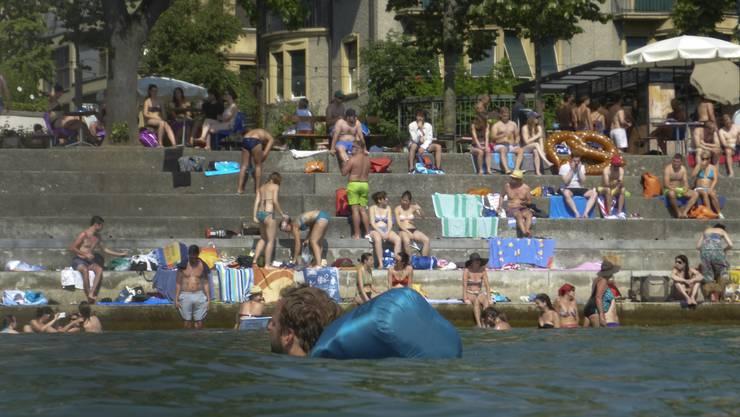 Leute sonnen sich am Rheinufer am Unteren Rheinweg in Basel