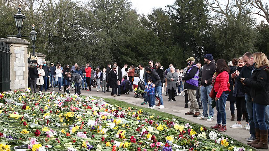 Menschen legen zu Ehren von Prinz Philip Blumen vor dem Schloss Windsor nieder. Foto: Gareth Fuller/PA Wire/dpa