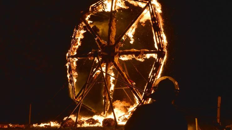 Das grosse Holzrad brennt ab.