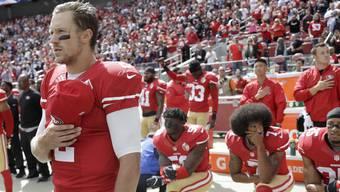 Protest während der obligaten Nationalhymne: 49ers-Quarterback Colin Kaepernick (2. v. r.) und einige seiner Mitspieler stehen nicht auf. Der weisse Teamkollege Blaine Gabbert (l.) hingegen zollt der Hymne den üblichen Respekt. Im Hintergrund reckt Rashard Robinson die geballte Faust im Black-Power-Stil.