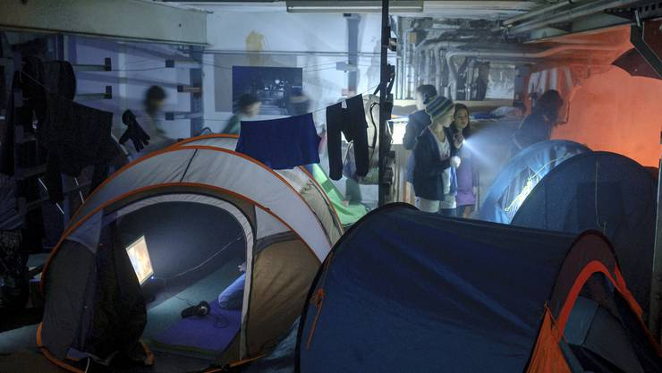 Mit Taschenlampen im Dunkeln gehen die Kinder auf Kartonpfade zwischen die Zelte.