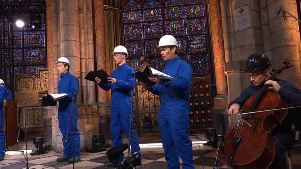 HANDOUT - Cellist Gautier Capucon (r) und der Chor der Kathedrale Notre Dame zeichnen ein Weihnachtskonzert auf. Foto: Musique Sacree à Notre-Dame de Paris/MSNDP/AP/dpa
