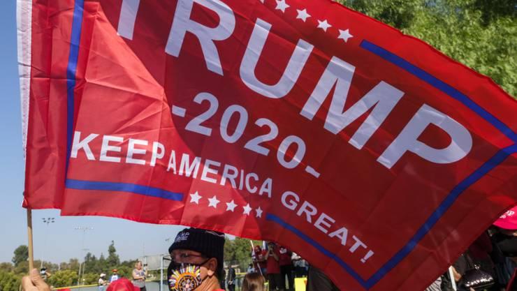 Ein Mann schwenkt eine Fahne während einer Kundgebung zur Unterstützung des US-Präsidenten Trump. Foto: Ringo Chiu/ZUMA Wire/dpa