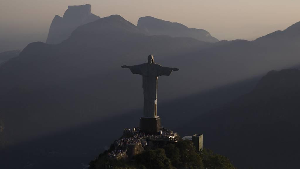 Franzosen klettern auf Arme von Christusstatue in Rio de Janeiro