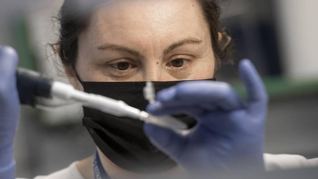 Eine Laborantin in Bellinzona bereitet eine Probe mit extrahierter RNA für einen PCR-Test vor, bei denen Mutationen des Coronavirus erkannt werden sollen. (Archivbild)