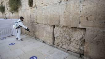 dpatopbilder - Ein Arbeiter verteilt Desinfektionsmittel als Vorsichtsmaßnahme gegen das Coronavirus an der Klagemauer, der heiligsten Stätte, an der Juden in Jerusalem beten können. Foto: Sebastian Scheiner/AP/dpa