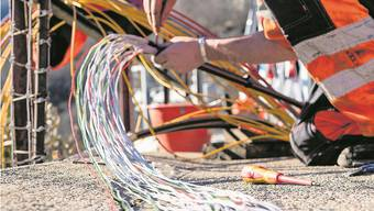 Ein Arbeiter montiert Glasfaserkabeln. Carlo Reguzzi/Ti-Press
