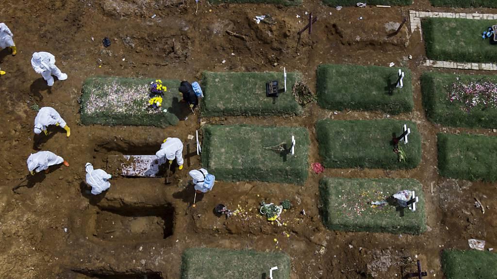ARCHIV - Särge im indonisischen Medan werden auf einem speziell für Corona-Opfer vorgesehenen Friedhof zu Grabe getragen. Foto: Binsar Bakkara/AP/dpa