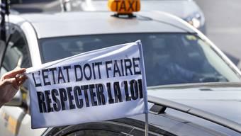 Genfer Taxifahrer wollen sich gegen die Vorlage zur Legalisierung des Fahrdienstes Uber wehren. Das Bild zeigt eine Protestaktion gegen den Fahrdienst. (Archivbild)