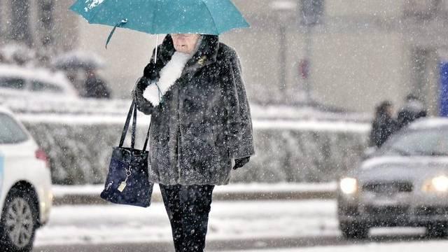Eine Fussgängerin im Schneetreiben in Zürich