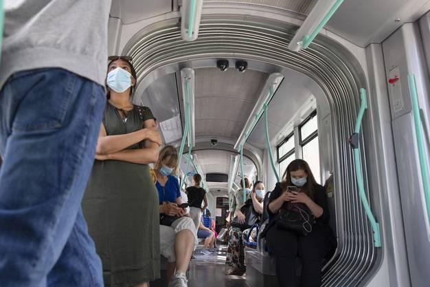 Passagiere mit Masken in einem Tram in Genf.