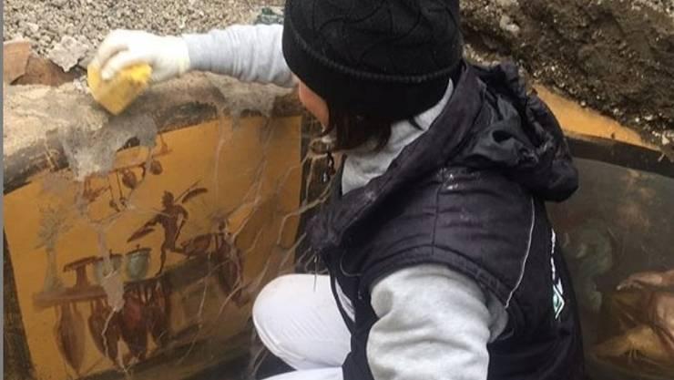 Eine Archäologin legt Fresken frei, welche die Theke eines Thermopoliums - eines Strassenimbisses - in Pompeji verzieren. Die zerfallene Stätte ist zwar saniert worden, aber ein Drittel der Stadt ist noch nicht freigelegt. (Instagram Massimo Osanna)