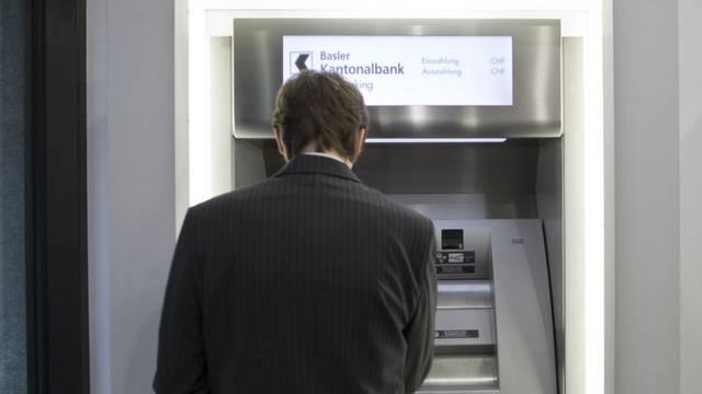 Ein Kunde hebt an einem Geldautomaten am Hauptsitz der Basler Kantonalbank an der Spiegelgasse in Basel Geld ab (Archiv)