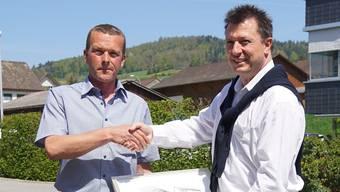 Vizeammann Thomas Lindenmann (links) übergibt Guido Reber, CEO der Sensato AG, ein Bild mit Ansichten von Seengen.
