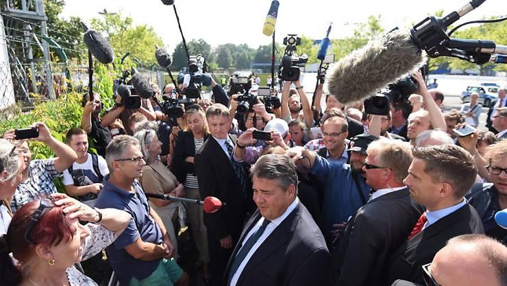 Der deutsche Vizekanzler Sigmar Gabriel spricht nach den rechtsradikalen Krawallen im ostdeutschen Heidenau mit Anwohnern und Journalisten
