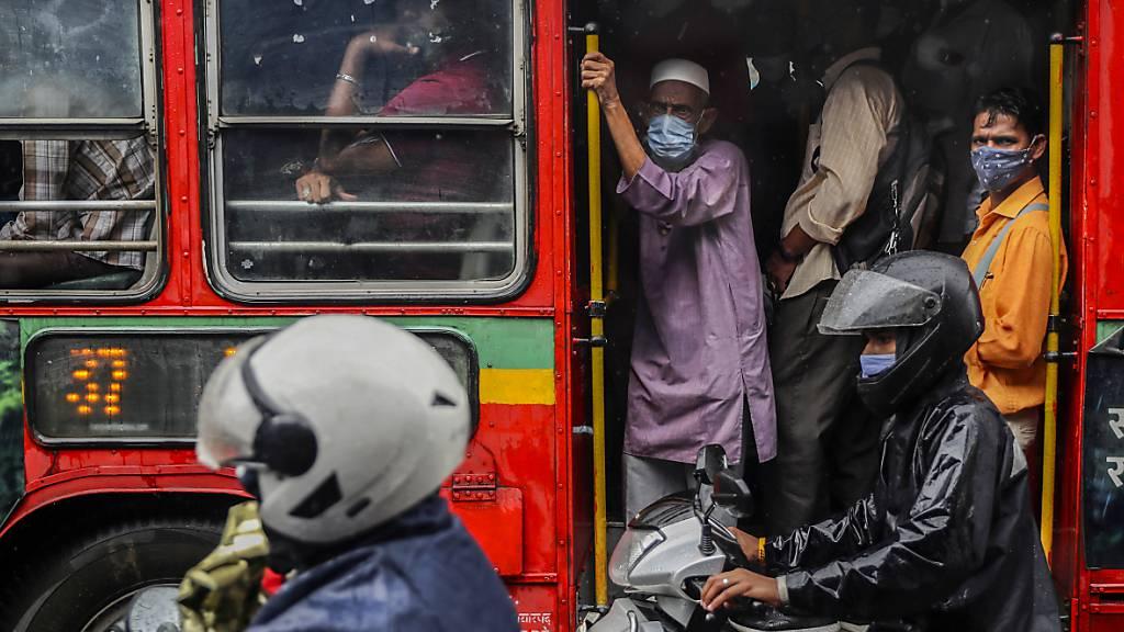 Personen tragen Mund-Nasen-Schutz, als sie in einem voll besetzten Bus fahren. Foto: Rafiq Maqbool/AP/dpa