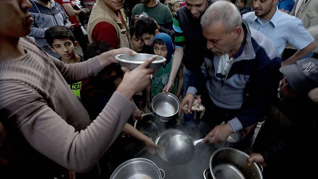 Essensausgabe durch eine Hilfsorganisation in Gaza Stadt zum Fastenbrechen während des Ramadan.