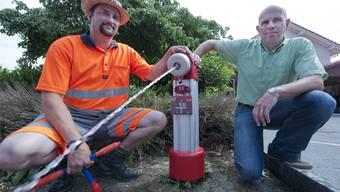 Brunnenmeister Mario Probst (links) und Gemeinderat Martin Schönmann zeigen an einem Hydranten beim Räberhus, wie das öffentliche Wassernetz geknackt werden kann – zum Schaden der Allgemeinheit. Marcel Bieri