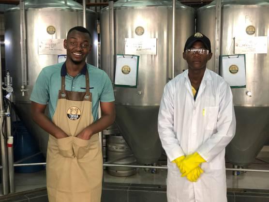 Damian Mosoka und Denis Mhenga, Mitarbeiter der Twiga Brewery, vor den Gärtanks