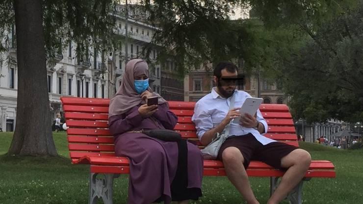 Das Bild des Anstosses: Eine verhüllte Frau mit Mundschutz auf einer Bank in Lugano.