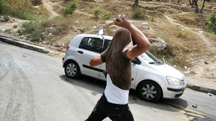Ein palästinensischer Jugendlicher macht sich daran, einen Stein auf ein mit israelischer Flagge dekoriertes Auto zu werfen. Steinewerfer sollen nach dem Willen der israelischen Justizministerin einfacher bestraft werden können. (Archiv)