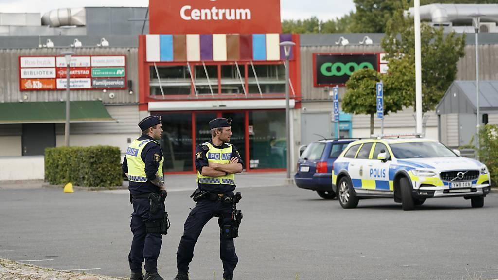 ARCHIV - Zwei Polizisten stehen am Tatort nach mutmaßlichen Schüssen im Stadtteil Nasby auf einem Parkplatz. Das EU-Land Schweden hat ein Problem: eine eskalierende Bandenkriminalität. Wird Schweden somit zum Gangster-Paradies - oder ist es das schon? Foto: Johan Nilsson/TT News Agency/AP/dpa
